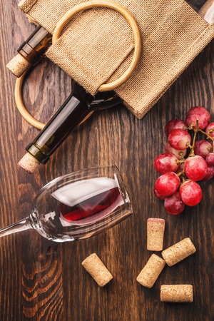 best regards: Glass with red wine, bottle and bunch of red grapes, wooden background Stock Photo