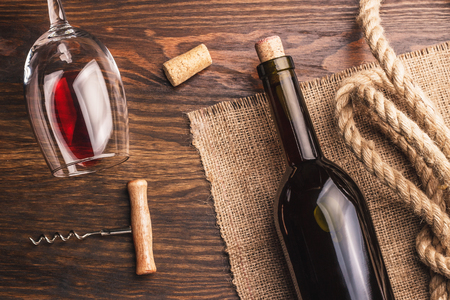 best regards: Glass with red wine, bottle, corkscrew and burlap, wooden background Stock Photo