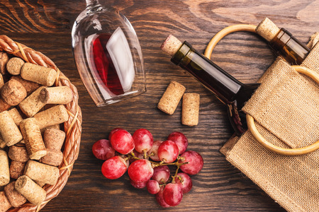 best regards: Glass with red wine, bottles and bunch of red grapes, wooden background