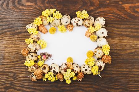 flores secas: Cap�tulo de los huevos de codorniz y decoraciones de flores secas, fondo de madera Foto de archivo