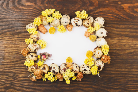 flores secas: Frame from quail eggs and dried flowers decorations, wooden background Foto de archivo