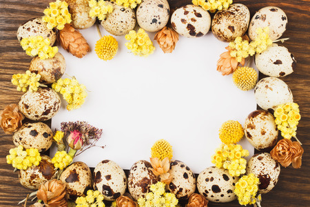 dried flowers: Easter frame from quail eggs and dried flowers, wooden background Stock Photo