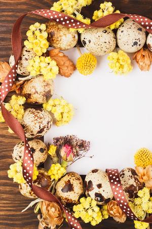 flores secas: Marco de Pascua de los huevos de codorniz y flores secas, fondo de madera