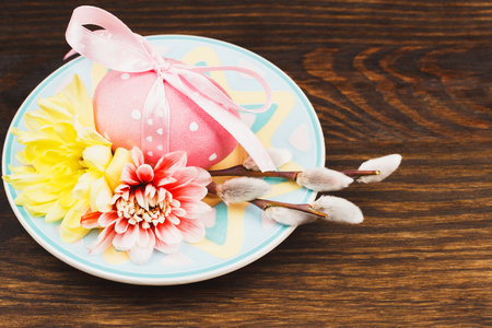 pink pussy: Pink Easter eggs on the decorative colorful plates, wooden background