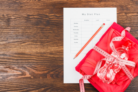diet plan: Diet plan, pencil and pink measuring tape, wooden background