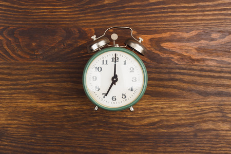 beat the clock: Green vintage alarm clock on the wooden background Stock Photo