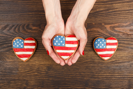 julio: Heart shaped cookie with American patriotic colors in the hands, wooden background