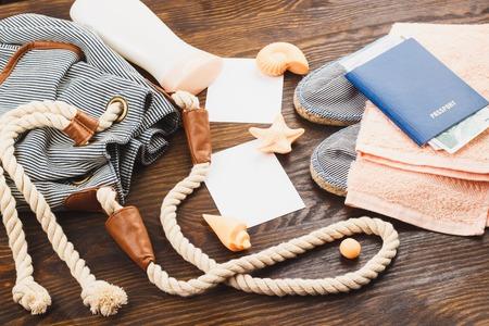 mochila de viaje: Mochila con par de alpargatas y conchas marinas en el fondo de madera