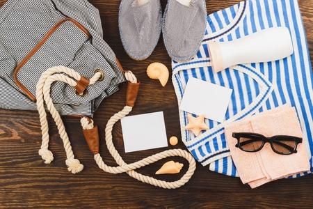 mochila de viaje: Mochila con par de alpargatas y t-corto en el fondo de madera