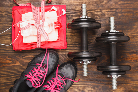 sports clothing: Sports items: sneakers, dumbbells, tape measuring and sports clothing on the wooden background