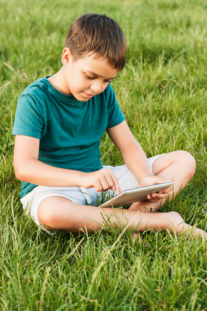 Young boy sitting on the green grass, holds a tablet in the hands, soft focus background Imagens