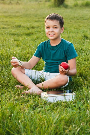 Young boy sitting on the green grass, holds a phone and apple, soft focus background