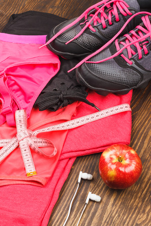 Sports items: sneakers, different sport clothing and apple on the wooden background