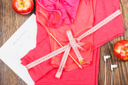Pink sport clothing with diet list, headphones and red apples on the wooden background