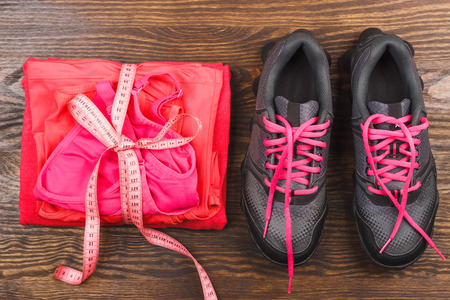 Sports items: sneakers, different sport clothing and tape measuring on the wooden background