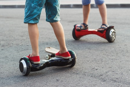 Young boys stands on the black gyro scooter outdoors, soft focus background Stock Photo