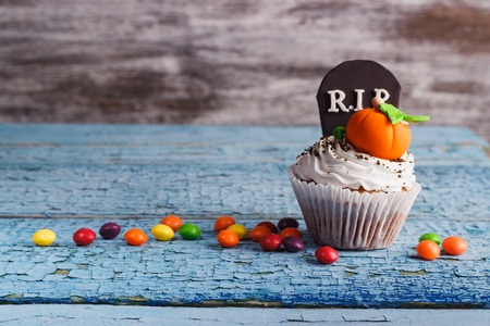 tombstones: Halloween cupcake with decorations: tombstone and pumpkin made from confectionery mastic, soft focus background