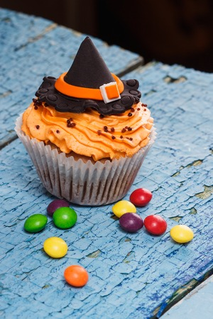 Halloween cupcake with decorations: Witches hat made from confectionery mastic, soft focus background