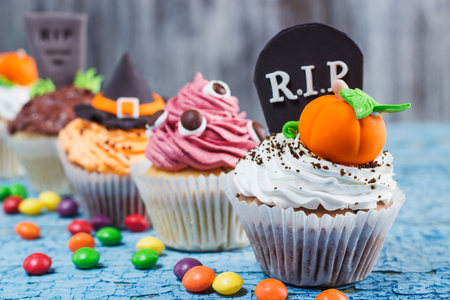 Halloween cupcakes with decorations: Witches hat, eyes and orange pumpkins made from confectionery mastic, soft focus background Stock Photo