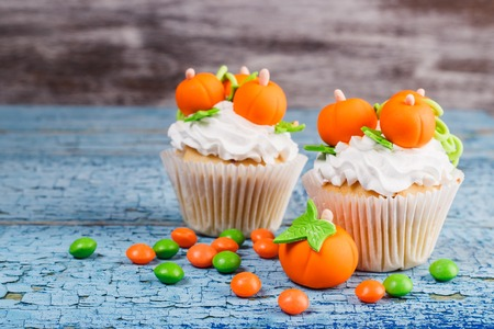 Halloween cupcake with decorations: orange pumpkins made from confectionery mastic, soft focus background