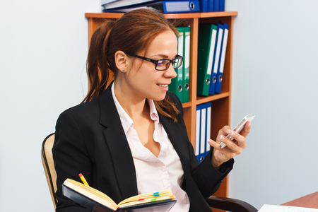 Working situation in the office: Woman holds a phone and a datebook, soft focus background