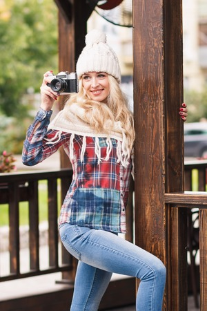plaid shirt: Young beautiful blonde in the knitted hat and plaid shirt holds old retro camera, soft focus background