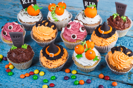 Halloween cupcakes with decorations: Witches hat, eyes, tombstone and orange pumpkins made from confectionery mastic, wooden background