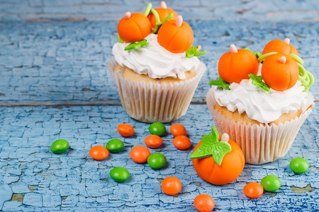 Halloween cupcake with decorations: orange pumpkins made from confectionery mastic, wooden background