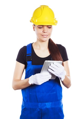 Woman builder in construction helmet and construction Jumpsuit holds tablet in the hands, isolated