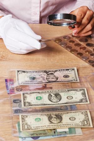 dolar: Una mujer mirando a la moneda Dólar través de una lupa, enfoque suave de fondo