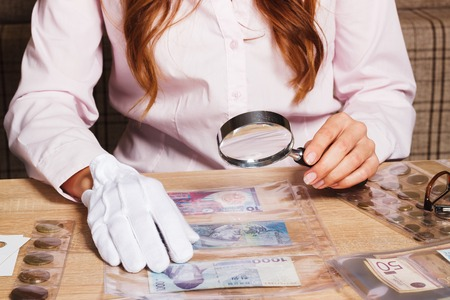 numismatist: Woman looking at the paper coin through a magnifying glass, soft focus background Stock Photo