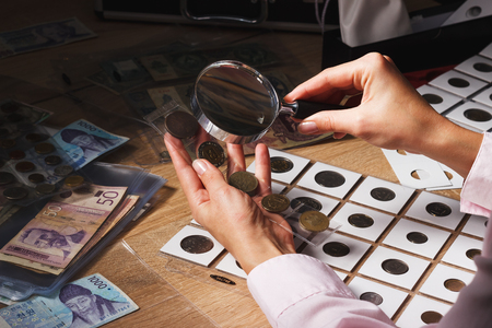 numismatist: Woman looking at the old coin through a magnifying glass, soft focus background Stock Photo