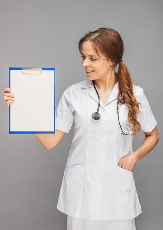 Woman doctor in the white medical uniform and a clipboard and stethoscope, gray background