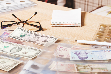numismatist: Different collectors coins and banknotes with a glasses, wooden background Stock Photo