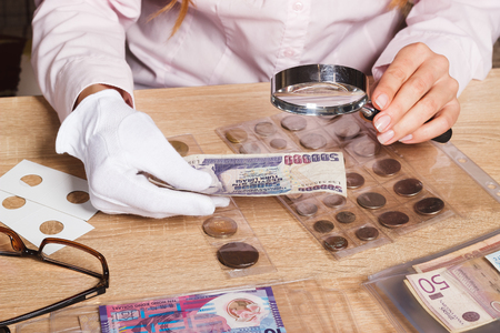 Woman looking at the Turkish lira through a magnifying glass, soft focus background