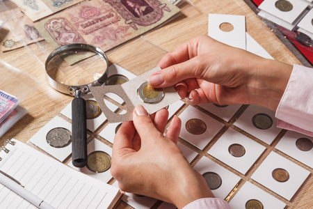 Woman looking at old collector s coin, soft focus background