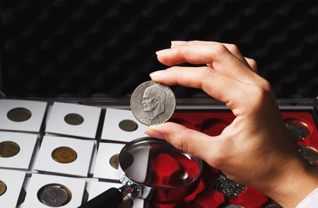 numismatist: Woman looking at the collectors Dollar coin, soft focus background Stock Photo