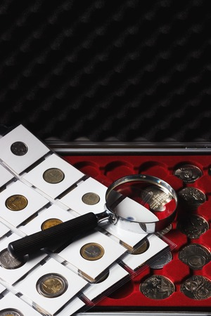 numismatist: Different size collectors coins in the box and magnifying glass, soft focus background