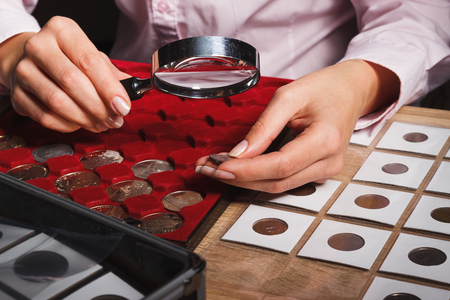 Woman looks at the coin through a magnifying glass, soft focus background