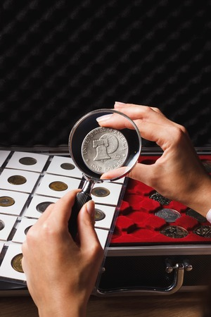 Woman looks at the dollar through a magnifying glass, soft focus background