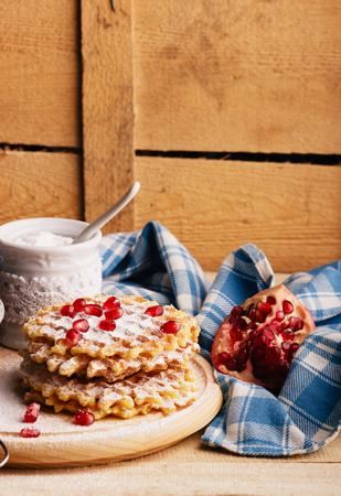 Few waffles and sugar bowl with sugar powder, soft focus background