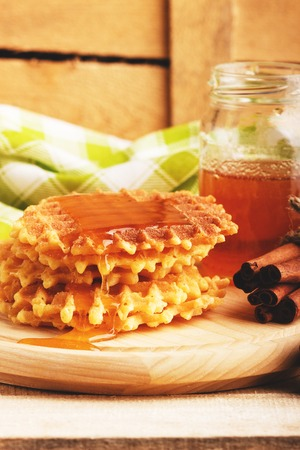 Few waffles, cinnamons sticks and glass with flowers honey, soft focus background Stock Photo