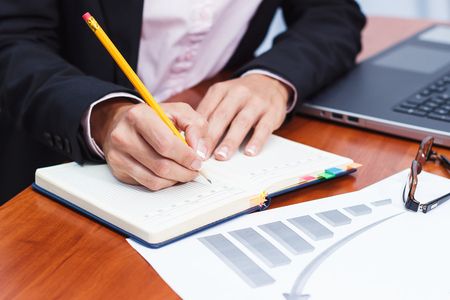 Business concept: Hands with a pencil, notebook and few graphs, soft focus background