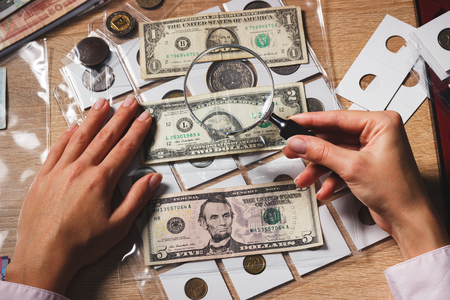 Hands with a set of old collectible dollars in the pockets through the magnifying glass, soft focus background