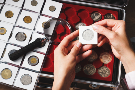 Box with collectible coins in the cells and a page with coins in the pockets, soft focus background Stock Photo
