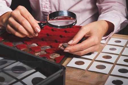 Box with collectible coins in the cells and a hand with coin through the magnifying glass, soft focus background Stock Photo