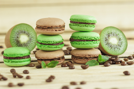 Green and brown french macarons with kiwi, coffee beans and mints decorations, soft focus background Stock Photo