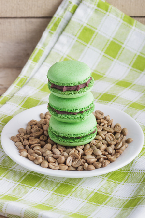 green bean: Green macarons on the plate with green coffee beans, soft focus background