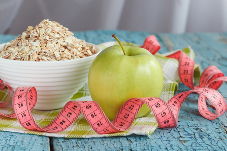 ration: Bowl of oatmeal, green apple and tape measuring on the wooden background