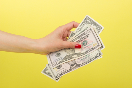 Fifty, five and one dollars in the womans hand, on the yellow background Stock Photo